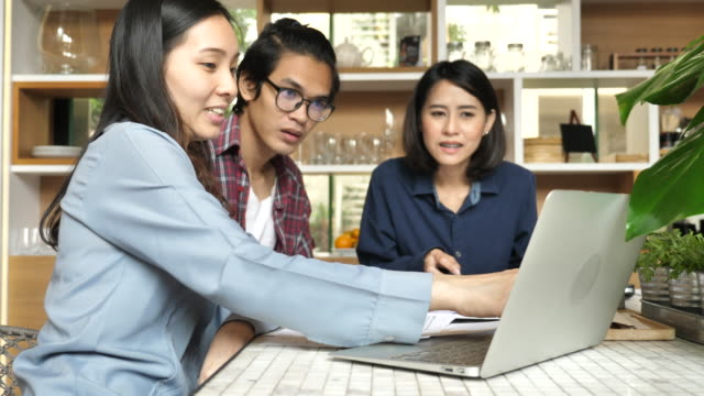Financial Consultation advisor explaining investment graphs to Asian couple at home