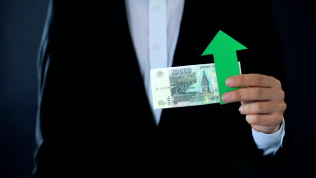 финансовый эксперт, держащий российские рублевые банкноты, показывающие большие пальцы вниз, рост - expert стоковые видео и кадры b-roll