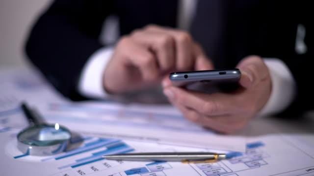 финансовый эксперт делает расчеты по гаджету, изучая статистику на диаграммах - expert стоковые видео и кадры b-roll