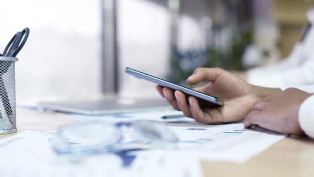 финансовый эксперт, печатающий на смартфоне в офисе, очки, лежащие на столе - expert стоковые видео и кадры b-roll