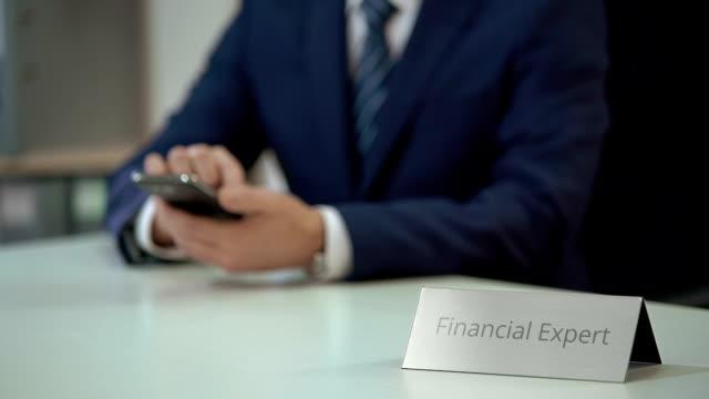 финансовый эксперт с помощью мобильного приложения на смартфоне, анализируя ситуацию на рынке - expert стоковые видео и кадры b-roll