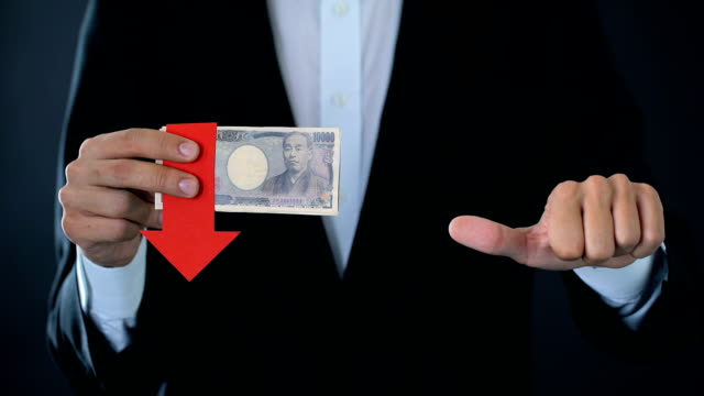 Financial expert with japanese yen banknotes showing thumbs up and down, falling