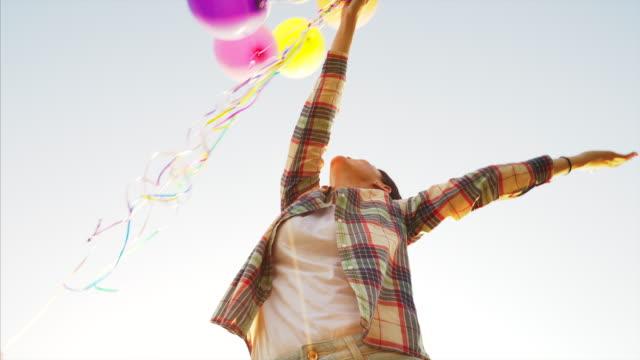 vídeos de stock e filmes b-roll de find joy in every little thing. - mulher balões