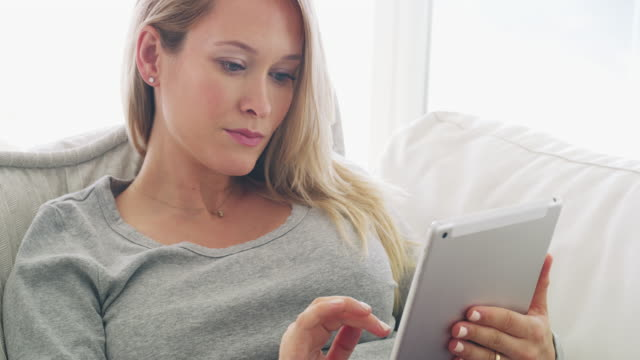 Finding all the prenatal information she needs online 4k video footage of a pregnant woman sitting on her living room sofa at home using a digital tablet candid stock videos & royalty-free footage