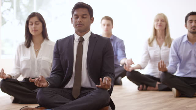 Finding Work-life Balance A multi-ethnic group of hardworking coworkers take time to meditate at work to maintain a healthy stress-free lifestyle. life balance stock videos & royalty-free footage
