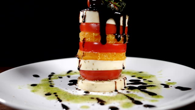 Fine cuisine in restaurant. Pouring vinegar sauce on mozzarella salad in slow motion. food footage on black background. Italian caprese salad with cheese. Healthy food and vegetarian concept. Full hd