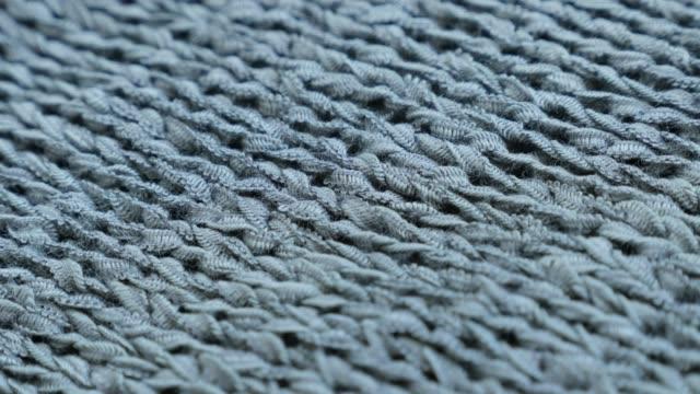fine green knitwork fine texture close-up slow tilt 4k 2160p 30fps ultrahd footage - knitting made sweater texture details shallow dof 3840x2160 uhd tilting video - cucitura video stock e b–roll