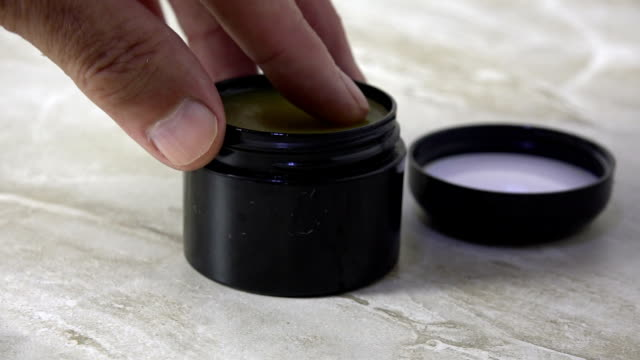 A finger dipping into a jar of CBD salve A finger dipping into a jar of CBD salve slow motion cannabidiol stock videos & royalty-free footage