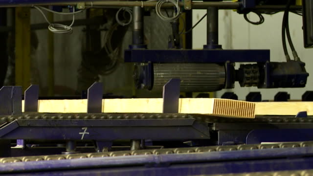 Finger Jointing Line in a Sawmill CU Preparing glued laminated lumber for finger jointing in a sawmill medium shot. human joint stock videos & royalty-free footage