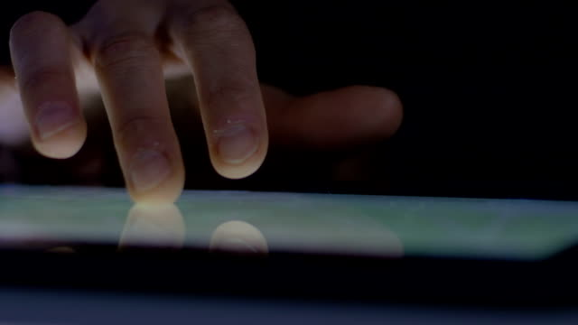finger of young woman using touchscreen of tablet computer video