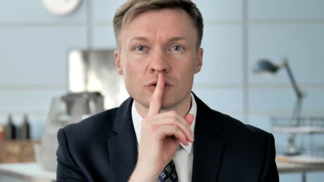 finger on lips, businessman gesturing silence - cisza filmów i materiałów b-roll