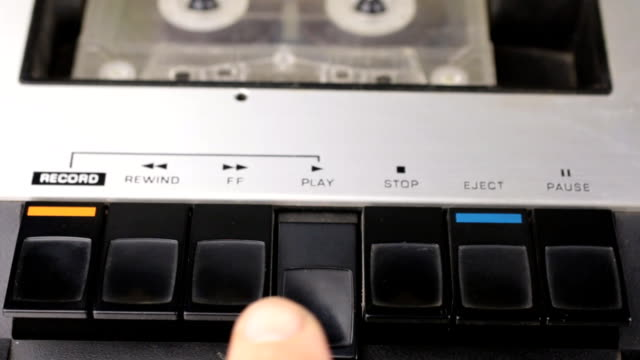 Finger press on play button and stop. Retro cassette tape player.