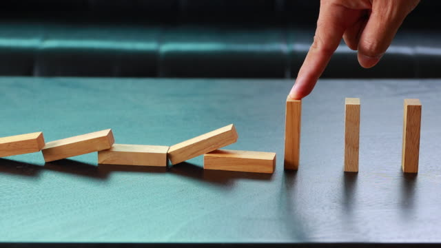 finger stopping the domino effect