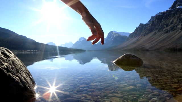 Finger touches surface of mountain lake, spectacular landscape video