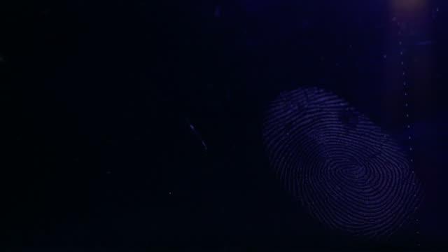 A fingerprint on a dark surface being scanned