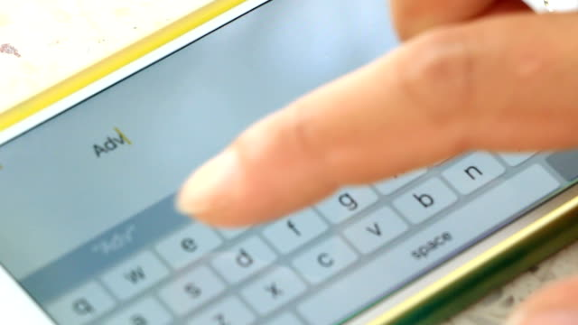 Fingers typing message on her smart phone touch screen.