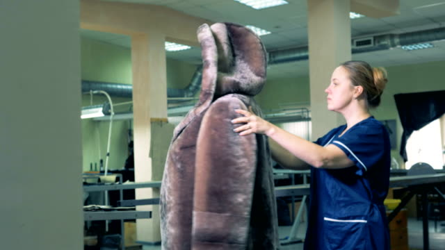 finished fur coat is getting inspected by a seamstress - sarta video stock e b–roll