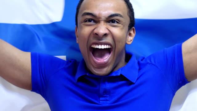 vídeos de stock e filmes b-roll de finnish fan celebrates holding the flag of finland in slow motion - liga desportiva