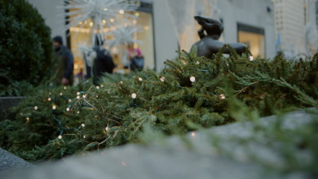 Fir tree in foreground crowd in background Christmas video