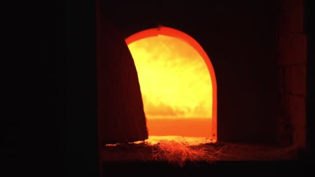 Fire burns in the factory stone oven Fire burns in the oven of the factory producing blown glass furnace stock videos & royalty-free footage