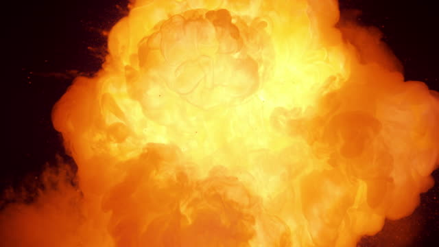 SLO MO Fire cloud bursting from black background Slow motion close up locked down shot of a fire cloud bursting from black background. burst stock videos & royalty-free footage