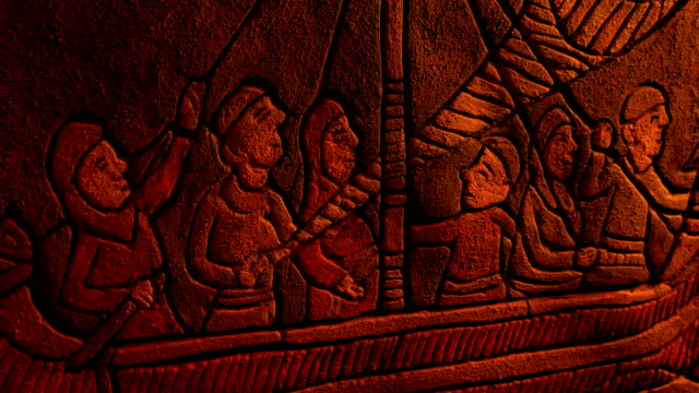 Fire Flickers On Artwork Of Medieval Ship Sailing Middle ages stone carving showing men on long boat in firelight european culture stock videos & royalty-free footage