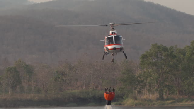Fire helicopter with water tank on the forest mountain