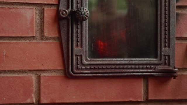 Fire is burning in an enclosed brick fireplace video