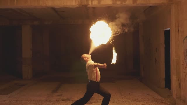 fire show artist breathe fire in the dark, slow motion - mostrare video stock e b–roll