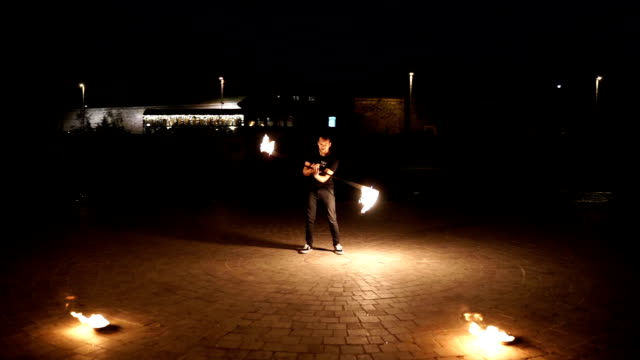 Fire show. Young man juggles with fire.Night performance. Fire show. Young man juggles with fire.Night performance. pyrotechnic effects stock videos & royalty-free footage