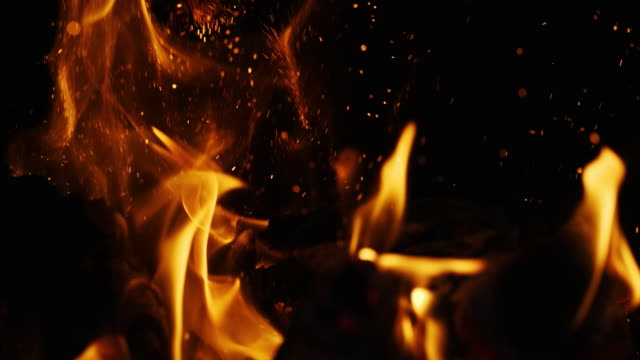 Fire sparks moving on dark at black background coming from brightly burning warm