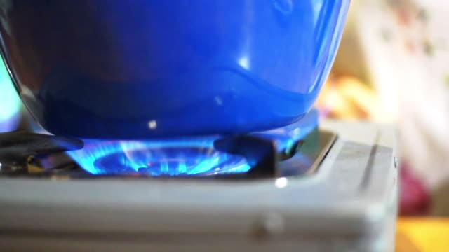 vídeos de stock e filmes b-roll de fire stove with blue pot - inflamável