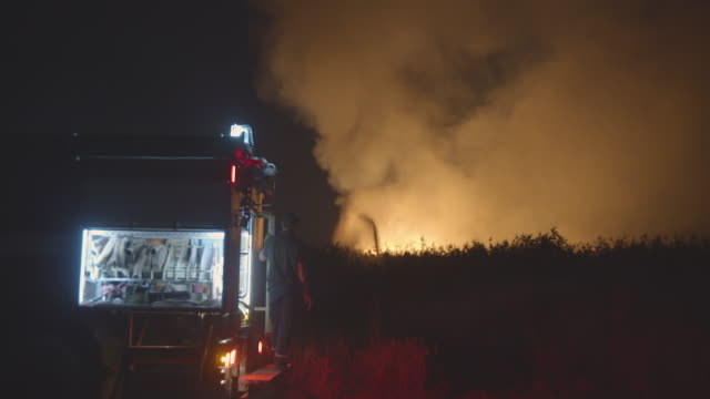 fire truck with flashing light on background burning field - tubo flessibile video stock e b–roll