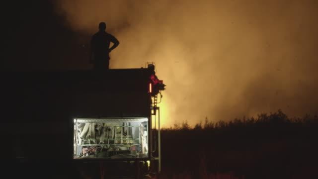brandbil med blinkande ljus på bakgrund brinnande fält - släcka bildbanksvideor och videomaterial från bakom kulisserna