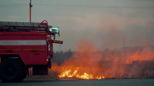 brandbil med blinkande ljus på bakgrunden brinnande gräs fält. brandbil på bakgrund av brinnande gräs på fältet under skogsbrand. räddning och förebyggande av naturkatastrofer. - släcka bildbanksvideor och videomaterial från bakom kulisserna