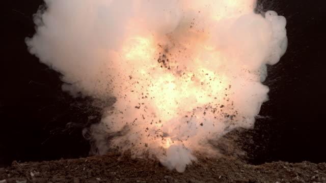 Fireball exploding out of dirt, slow motion video
