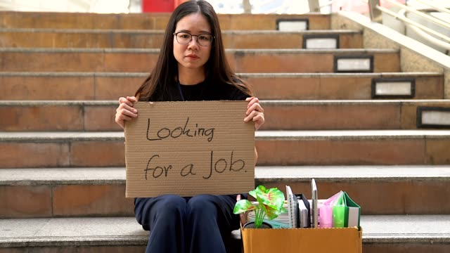 fired office worker women begging for a job sitting with homeless begging for help on the street.the economic crisis, economic reform concept.white collar employee being fired her sitting on the sidewalk to begging a new job. - unemployment stock videos & royalty-free footage