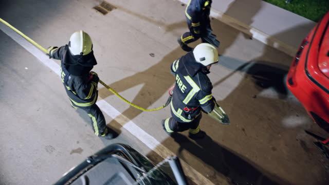 vídeos de stock, filmes e b-roll de cs bombeiro carregando a tesoura hidráulica para o carro caiu no local do acidente à noite - bombeiro