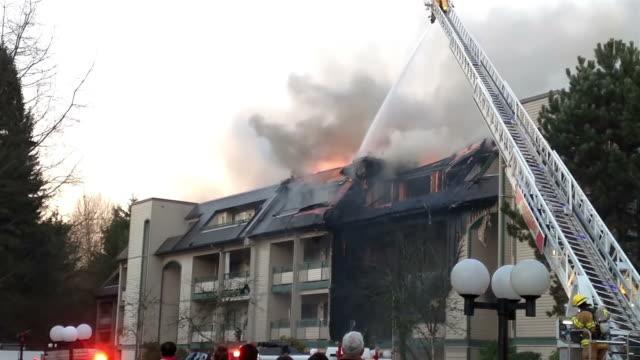 stockvideo's en b-roll-footage met firefighter crews battling apartment complex fire - ladder