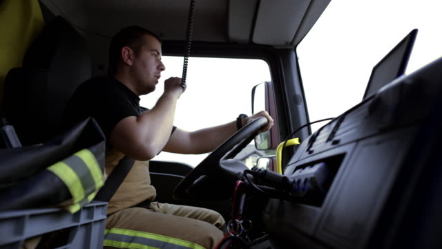 Firefighter driving a fire engine to the scene and communicating over the CB radio video