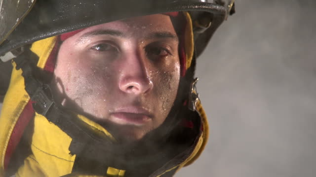 Firefighter looking at camera through smoke, slow motion video