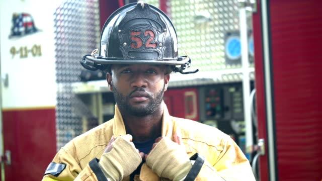 vidéos et rushes de pompier mettant sur le casque - uniforme