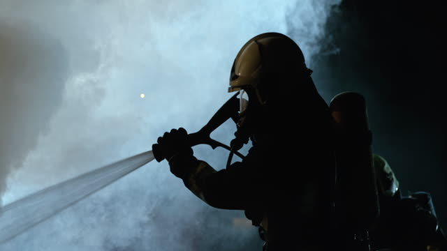 SLO MO Firefighter putting out a fire at night video