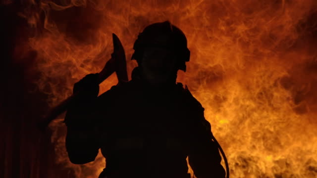 firefighter working. fire is raging. in slow motion. - incendio doloso video stock e b–roll