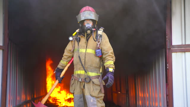 firefighter working. fire is raging. - incendio doloso video stock e b–roll