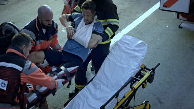 vídeos de stock e filmes b-roll de firefighters and paramedics lifting the injured male cyclist onto the stretcher at the scene of the accident - resgate