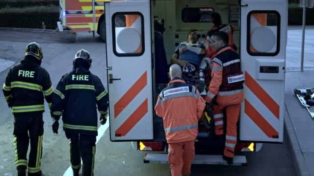 Feuerwehrleute und Sanitäter schieben die Bahre mit einem verletzten männlichen Radfahrer in den Krankenwagen – Video
