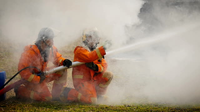 firefighters fighting a fire operation, foam spray by high pressure nozzle to truck fire after the accident - firefighter stock videos and b-roll footage