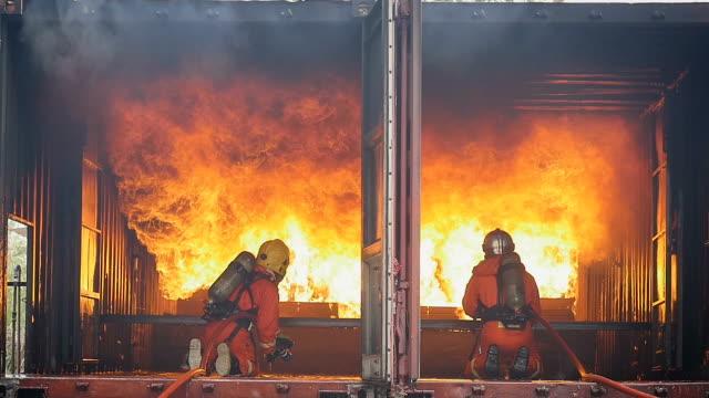 Feuerwehrleute kämpfen ein Feuer Betrieb, Spritzwasser durch Hochdruckdüse Surround mit Rauch Feuer – Video