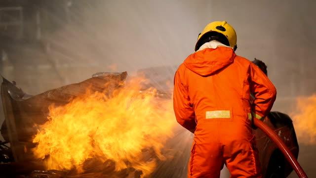 brandmän bekämpa en brand drift, vattenspray av högtrycksmunstycket till brand surround med rök - släcka bildbanksvideor och videomaterial från bakom kulisserna